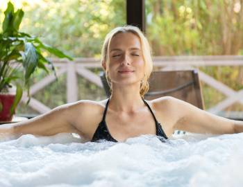 woman relaxing in hot tub in summer